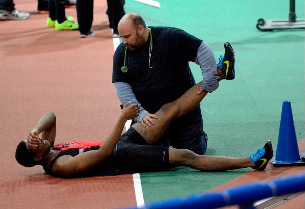 man holding athlete's feet on the ground
