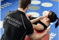 Trainer assisting woman